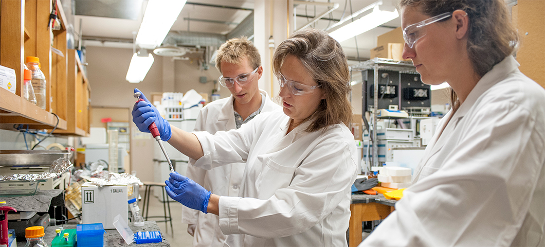 Photo of a graduate mentor pipetting with an undergraduate and another graduate student.