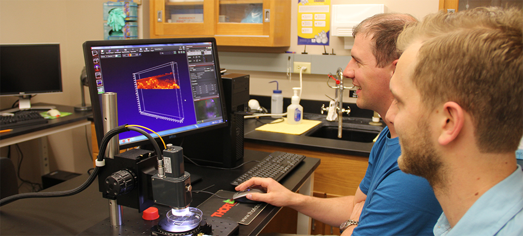 Photo of a graduate mentor with an undergraduate in microscopy lab.