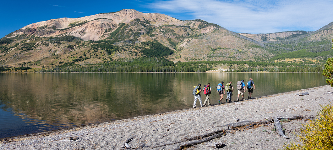 Photo of students hiking past a lake with the mountains in the distance.